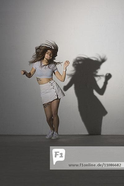 Volle Länge der fröhlichen Frau  die vor grauem Hintergrund tanzt.