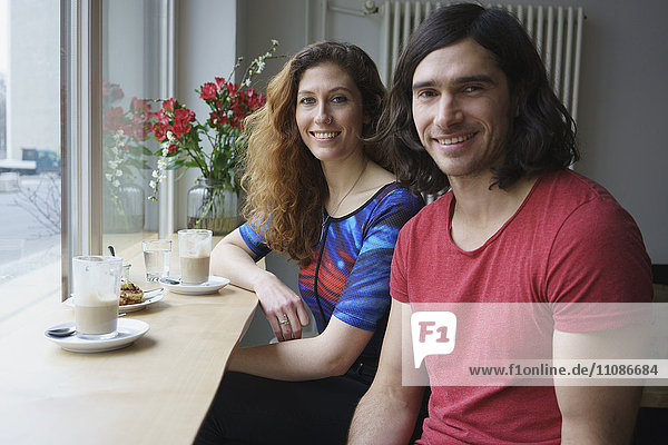Portrait of smiling friends having coffee at cafe