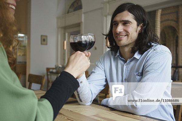 Freunde stoßen im Café auf Wein an.
