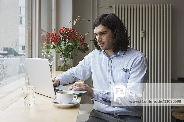 Mann mit Laptop beim Kaffeetrinken im Cafe