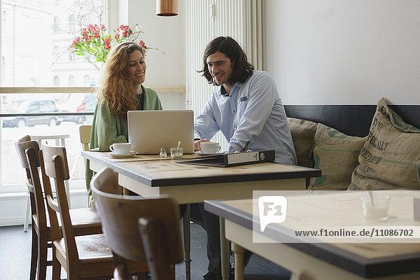 Fröhliche Freunde  die im Café auf den Laptop schauen