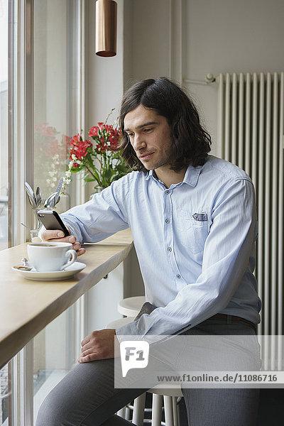 Mann mit Smartphone beim Kaffeetrinken im Cafe