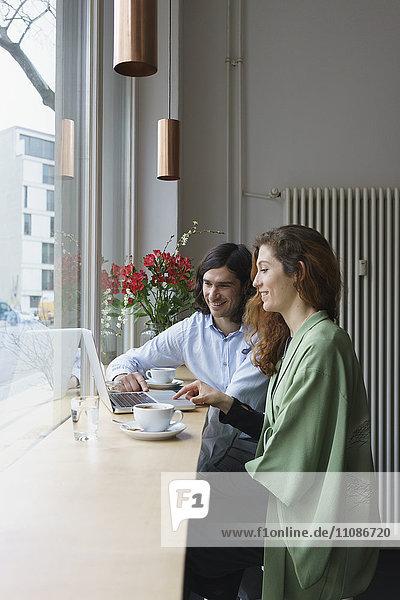 Lächelnde Freunde beim Kaffeetrinken im Cafe
