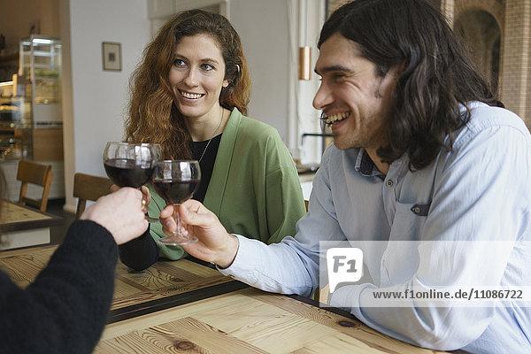 Fröhliche Freunde beim Weintrinken im Cafe
