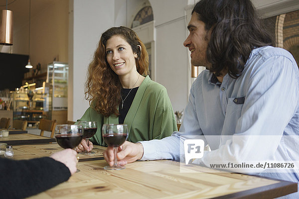 Lächelnde Freunde beim Weintrinken im Cafe