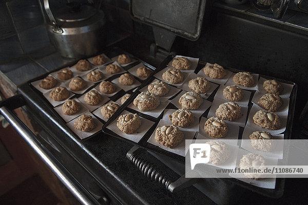 Hochwinkelansicht der auf Backblechen angeordneten Kekse in der Küche