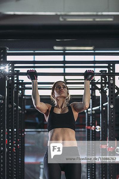 Vorderansicht der Sportlerin beim Kinn-Up im Fitnessstudio