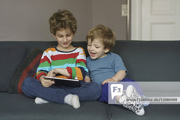 Happy siblings looking at digital tablet while sitting on sofa at home