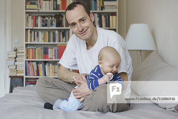 Vater und Sohn sitzen zu Hause auf dem Bett gegen das Bücherregal.