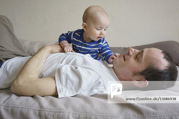 Seitenansicht des Vaters liegend mit Sohn auf dem Bett zu Hause