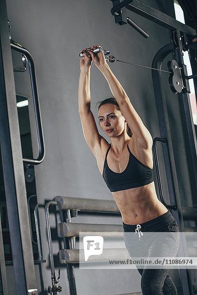 Entschlossener junger Sportler beim Training im Fitnessstudio