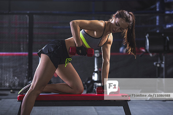 Junge Sportlerin beim Heben von Gewichten im Fitnessstudio