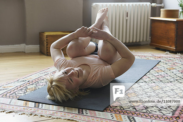 Happy woman exercising on mat in living room