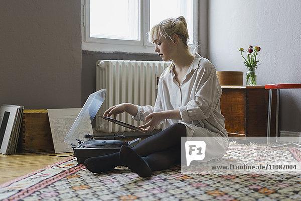 Volle Länge der Frau  die im Sitzen zu Hause Schallplatte spielt