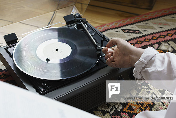 Cropped image of woman playing record at home