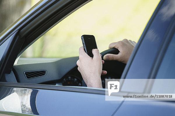 Beschnittenes Bild der Hand mit dem Handy im Auto