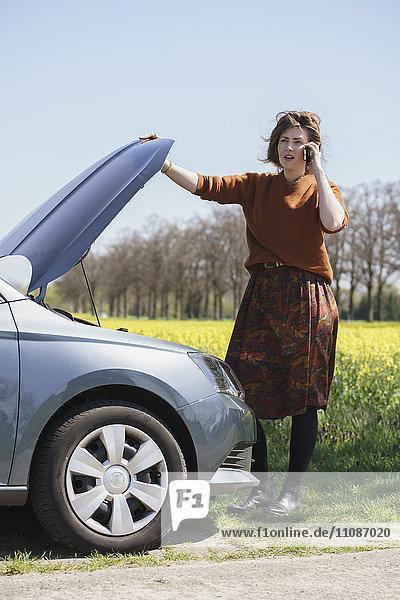 Junge Frau  die auf dem Handy kommuniziert  während sie im Auto steht.