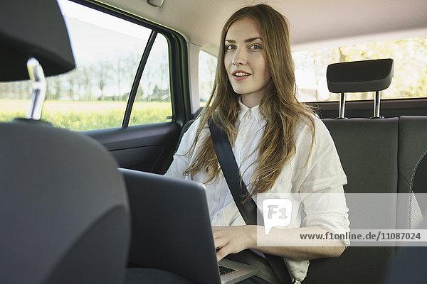 Portrait der Geschäftsfrau mit Laptop im Auto