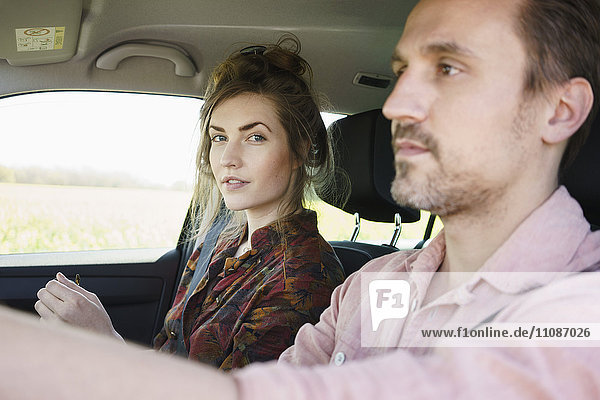 Mann fährt im Sitzen neben Frau im Auto