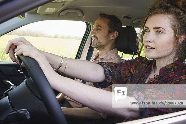 Frau beim Fahren neben Mann im Auto sitzend