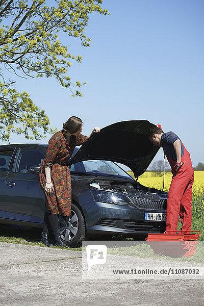 Frau  die ein Auto am Straßenrand repariert.