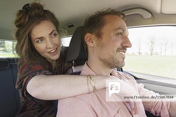 Junge Frau umarmt Mann beim Autofahren