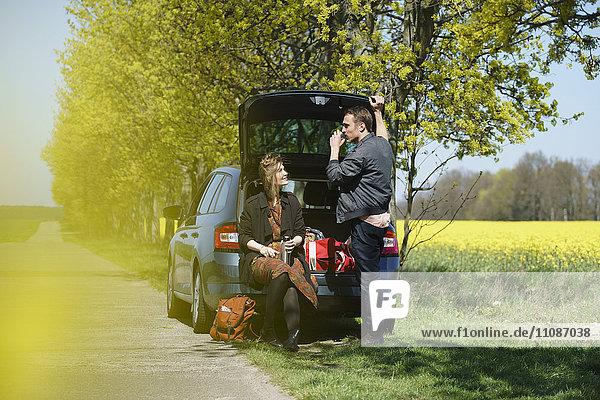 Frau im Kofferraum neben Mann am Straßenrand bei Sonnenschein