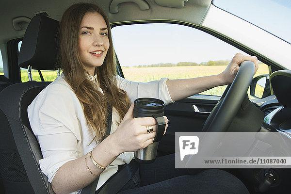 Porträt einer Geschäftsfrau mit isoliertem Getränkebehälter beim Autofahren