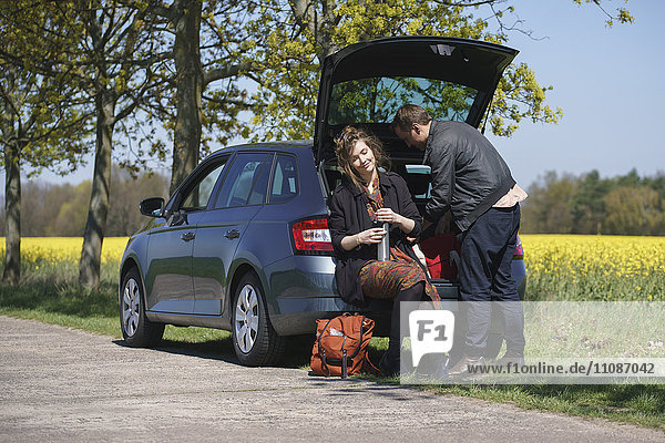Frau sitzend im Kofferraum neben Mann am Straßenrand