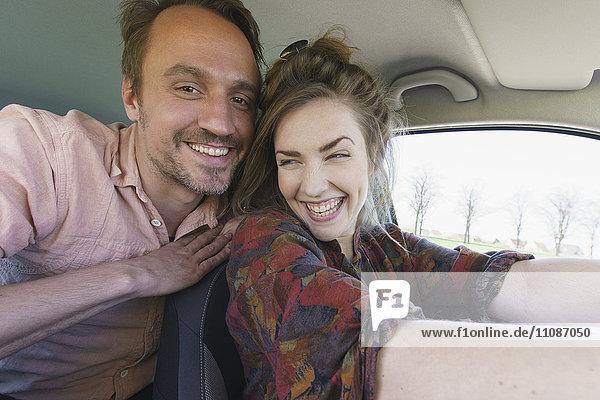 Glücklicher Mann genießt mit Frau beim Autofahren