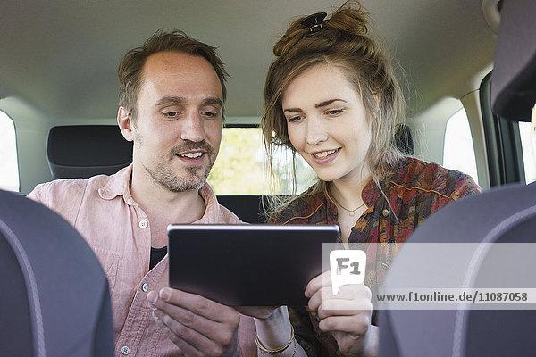 Glückliches Paar mit digitalem Tablett auf Reisen im Auto