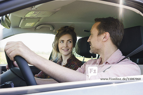 Lächelndes Paar  das sich beim Autofahren ansieht.