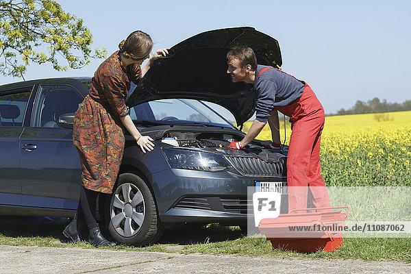 Frau sieht lächelnde Mechanikerin beim Reparieren eines Autos am Straßenrand