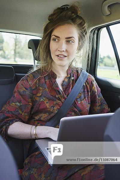 Nachdenkliche junge Frau mit Laptop im Auto
