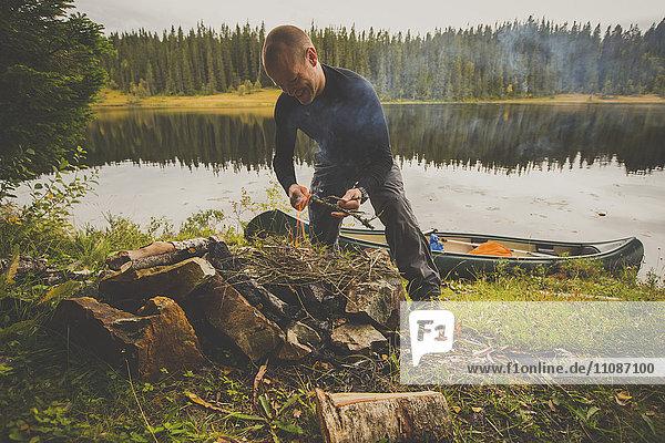 Fröhlicher Wanderer beim Zubereiten von Speisen über dem Lagerfeuer am Seeufer im Wald