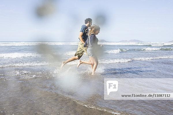 Seitenansicht des glücklichen Paares auf dem Weg zum Meer