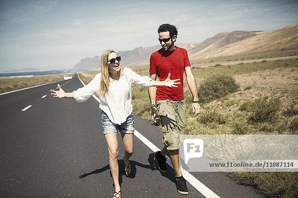 Volle Länge der glücklichen Frau im Gespräch mit dem Mann beim Gehen auf der Straße