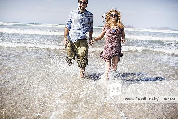Fröhliches Paar  das an einem sonnigen Tag im Meer läuft