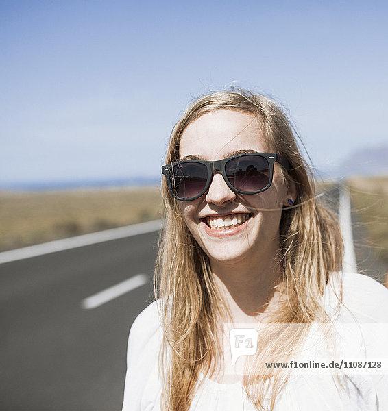 Lächelnde junge Frau mit Sonnenbrille auf der Straße