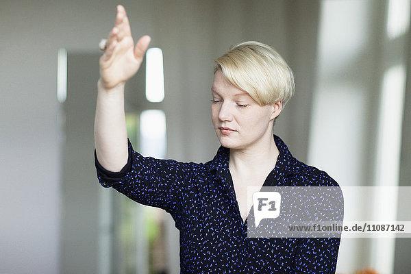 Schöne mittlere erwachsene Frau  die zu Hause mit geschlossenen Augen trainiert.