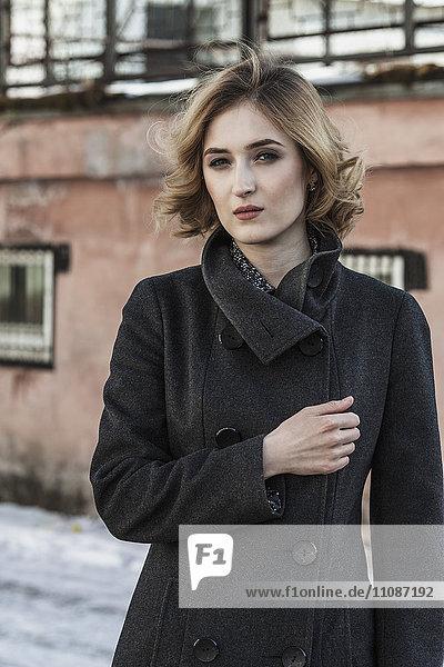 Porträt einer selbstbewussten jungen Frau mit langem Mantel im Freien
