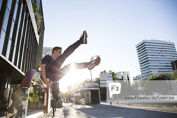 Spain  Madrid  man jumping over a fence in the city during a parkour session