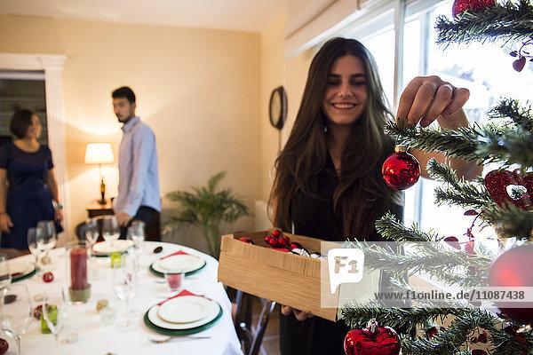 Frau schmückt den Weihnachtsbaum mit Freunden im Hintergrund