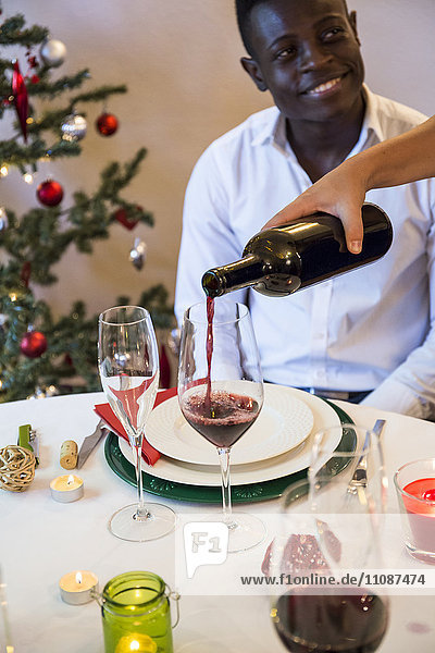 Woman serving wine to man at Christmas dinner