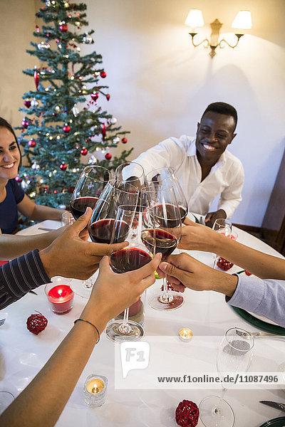 Freundestoast mit Wein während eines Weihnachtsessens