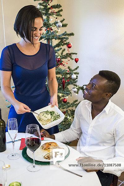 Frau serviert Kartoffelpüree zum Weihnachtsessen