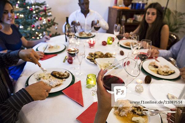 Freunde beim Weihnachtsessen mit Rotwein