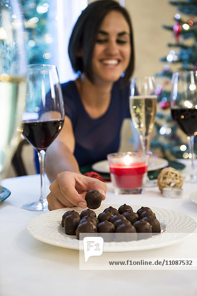 Woman picking a chocolate truffle during Christmas dinner