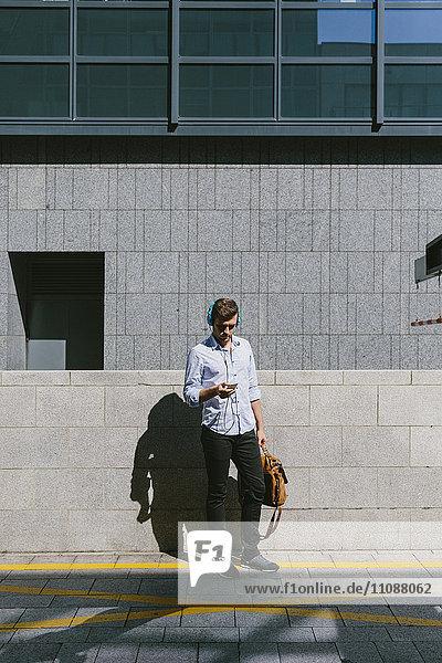 Irland  Dublin  Geschäftsmann mit Kopfhörern beim Blick auf das Handy