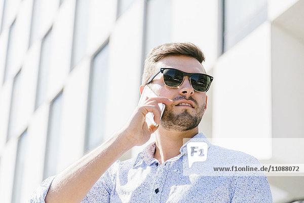 Porträt eines telefonierenden Geschäftsmannes mit Sonnenbrille